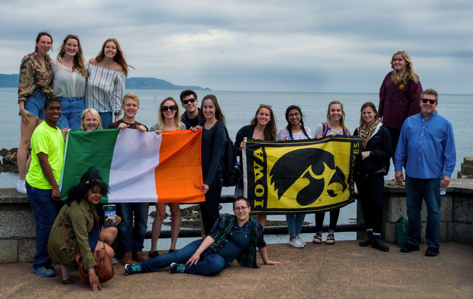 Group of students standing with ocean behind them holding an Irish flag and an American flag
