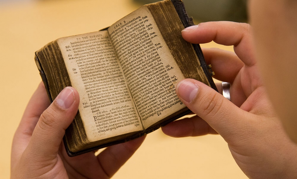 English student holding an old book